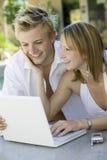 Jeunes couples utilisant l'ordinateur portable Photographie stock libre de droits