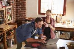 Jeunes couples utilisant l'ordinateur portable dans la cuisine, courbe Images libres de droits