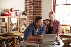 Jeunes couples utilisant l'ordinateur portable dans la cuisine, courbe Photo stock
