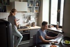 Jeunes couples utilisant l'ordinateur portable et le smartphone dans la cuisine image libre de droits