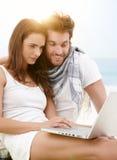 Jeunes couples utilisant l'ordinateur portable sur la plage Image stock