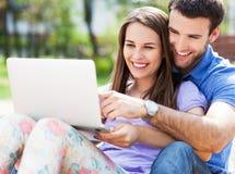 Jeunes couples utilisant l'ordinateur portatif à l'extérieur Photo libre de droits