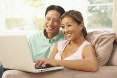 Jeunes couples utilisant l'ordinateur portatif à la maison Photos stock