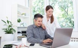 Jeunes couples utilisant l'ordinateur portatif Images stock