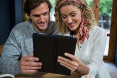 Jeunes couples utilisant la tablette à la table dans le cafétéria Photographie stock