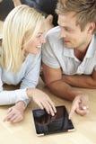 Jeunes couples utilisant le comprimé numérique Images libres de droits