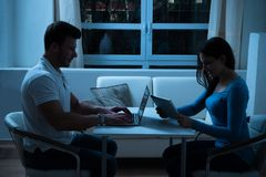 Jeunes couples utilisant le comprimé numérique et l'ordinateur portable Image stock