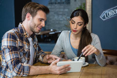 Jeunes couples utilisant le comprimé numérique tout en ayant le café Photographie stock