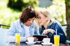 Jeunes couples utilisant le comprimé tout en se reposant ensemble au café Photographie stock