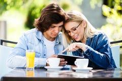 Jeunes couples utilisant le comprimé tout en se reposant ensemble au café Image libre de droits