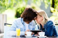 Jeunes couples utilisant le comprimé tout en se reposant ensemble au café Photos libres de droits