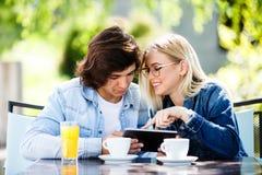 Jeunes couples utilisant le comprimé tout en se reposant ensemble au café Photos stock