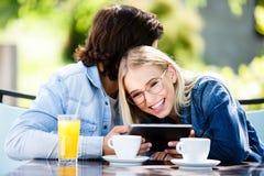 Jeunes couples utilisant le comprimé tout en se reposant ensemble au café Images libres de droits