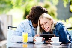 Jeunes couples utilisant le comprimé tout en se reposant ensemble au café Image stock