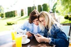 Jeunes couples utilisant le comprimé tout en se reposant ensemble au café Photo libre de droits
