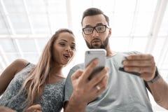 Jeunes couples utilisant le smartphone pour des achats en ligne photographie stock libre de droits