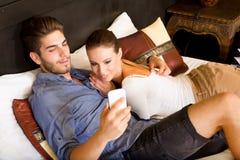 Jeunes couples utilisant le téléphone dans une chambre d'hôtel asiatique Photo libre de droits