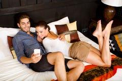 Jeunes couples utilisant le téléphone dans une chambre d'hôtel asiatique Images libres de droits