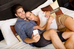 Jeunes couples utilisant le téléphone dans une chambre d'hôtel asiatique Image libre de droits