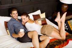 Jeunes couples utilisant le téléphone dans une chambre d'hôtel asiatique Photographie stock