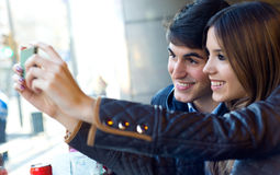 Jeunes couples utilisant le téléphone portable en café Photographie stock