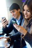 Jeunes couples utilisant le téléphone portable en café Images stock