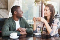 Jeunes couples utilisant les smartphones mobiles en café Photos stock