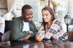 Jeunes couples utilisant les smartphones mobiles en café Photo stock