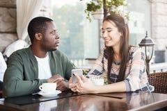 Jeunes couples utilisant les smartphones mobiles en café Photographie stock libre de droits