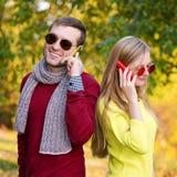 Jeunes couples utilisant téléphones portables Jeunes couples se parlant par le téléphone portable Photographie stock