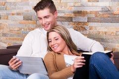 Jeunes couples utilisant un comprimé, souriant Photos stock