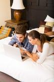 Jeunes couples utilisant un ordinateur portable dans une chambre d'hôtel asiatique Image libre de droits