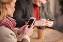 Jeunes couples vérifiant le media social tout en appréciant les boissons chaudes Images stock