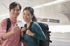 Jeunes couples vérifiant leur billet de train Photographie stock libre de droits