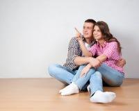 Jeunes couples visualisant le décor de leur nouvelle maison se reposant sur le plancher en bois nu précisant et discutant le plac Photo stock