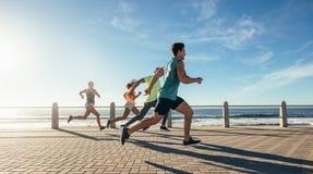 Jeunes coureurs sprintant sur le chemin de bord de l'océan Images libres de droits