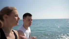 Jeunes courses de couples le long de la mer clips vidéos