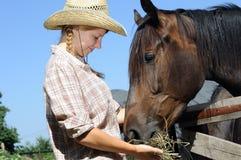 Jeunes cow-girl et cheval dans la ferme Images libres de droits