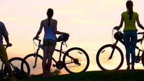 Jeunes cyclistes au beau coucher du soleil banque de vidéos