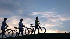 Jeunes cyclistes marchant sur la colline au coucher du soleil banque de vidéos