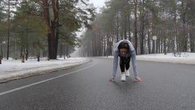 Jeunes débuts caucasiens attrayants de fille fonctionnant en parc neigeux en hiver avec des écouteurs Suivez le tir banque de vidéos