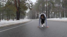 Jeunes débuts caucasiens attrayants de fille fonctionnant en parc neigeux en hiver avec des écouteurs Suivez le tir Mouvement len clips vidéos