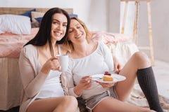 Jeunes dames décontractées appréciant la nourriture délicieuse Photo libre de droits