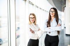 Jeunes dames d'affaires dans le hall de bureau au-dessus des fenêtres panoramiques Images libres de droits