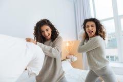 Jeunes dames enthousiastes souriant tout en combattant avec des oreillers Photos libres de droits