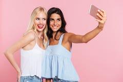 Jeunes dames faisant le selfie et le sourire d'isolement Photographie stock