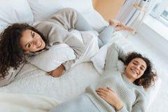 Jeunes dames joyeuses faisant la pause et se trouvant sur le lit Image stock