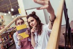 Jeunes dames satisfaites se photographiant et posant avec le livre photos stock