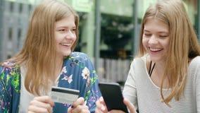 Jeunes dames utilisant un téléphone et tenir la carte de crédit images stock