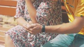 Jeunes dans des couples d'amour utilisant le smartphone se reposant sur le banc Jour venteux d'été banque de vidéos